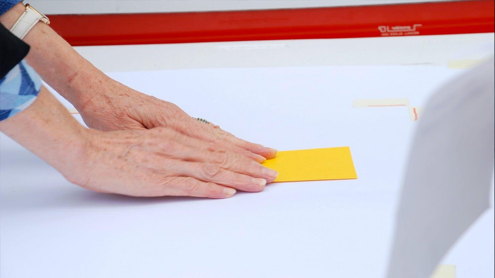 Copertina servizio Art&Community - mano che sposta un foglietto colorato