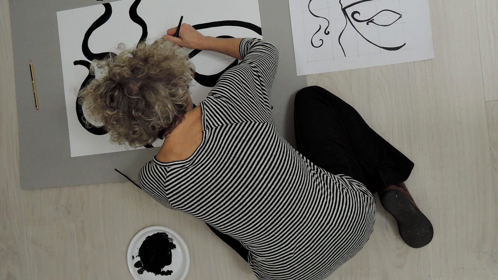 Copertina servizio formazione - donna dipinge una maschera durante un workshop